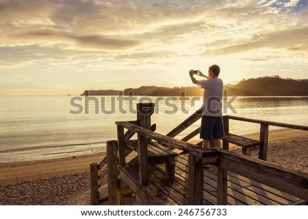 Taking photos of a beautiful sunset with a smartphone  - stock photo
