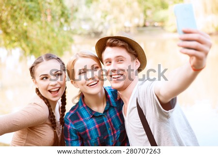 Taking picture. Smiling handsome man and two pretty women doing selfie on background of lake in park. - stock photo