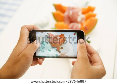 Taking pictures with the phone a plate of melon and ham - stock photo