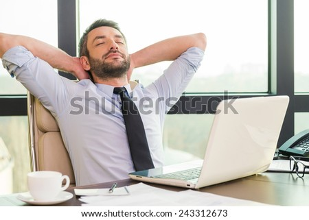 Taking time for a break. Handsome mature man in shirt and tie holding hands behind head and keeping eyes closed while sitting at his working place - stock photo