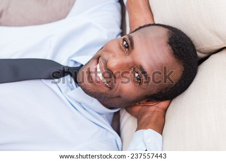 Taking time to for a minute break. Top view of handsome young African man in shirt and tie holding hands behind head and smiling while lying on the couch  - stock photo