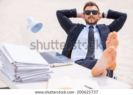 Taking time to relax. Relaxed young man in formalwear and sunglasses holding hands behind head and holding his feet on the table standing on sand - stock photo
