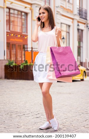 Taking with friend during shopping. Full length of beautiful young smiling woman holding shopping bags and talking on the mobile phone while standing outdoors - stock photo