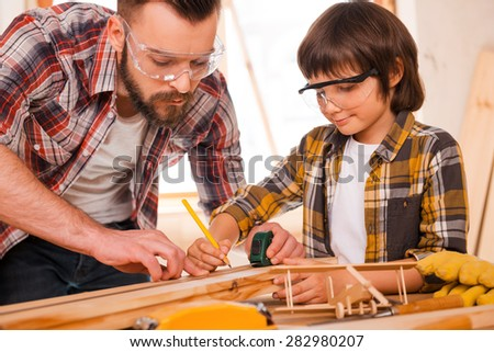 Talented workers. Concentrated young male carpenter teaching his son to work with wood in his workshop - stock photo