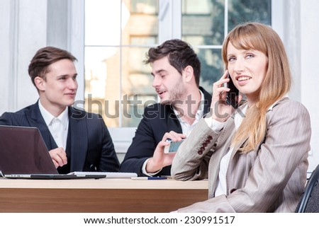 Talk on the phone. Businesswoman sitting at a table and talking on cell phone while her colleague businessmen talking in the background sitting at table - stock photo