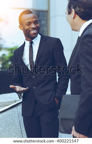 Talking about business. Two cheerful business men talking and gesturing while standing outdoors - stock photo