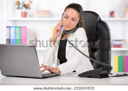 Talking at phone. Confident middle-aged businesswoman sitting at her working place and looking over shoulder - stock photo