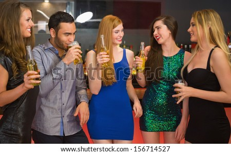 Talking friends at a bar drinking beer together on a night out - stock photo