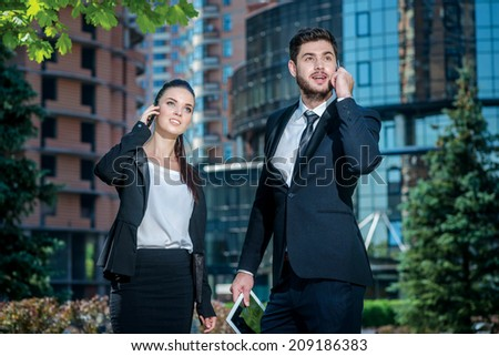 Talking on a cell phone with a client. Two businessmen walking on the street in the park and talking on a cell phone and looking up - stock photo