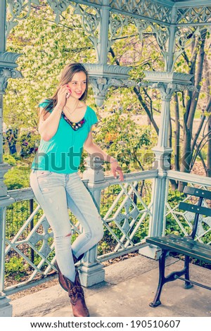 Talking on Phone. Dressing in a blue sleeveless top, fashionable jeans, brown boots, a blonde teenage girl is standing inside a pavilion, talking on her cell phone. Instagram Nashville effect. - stock photo