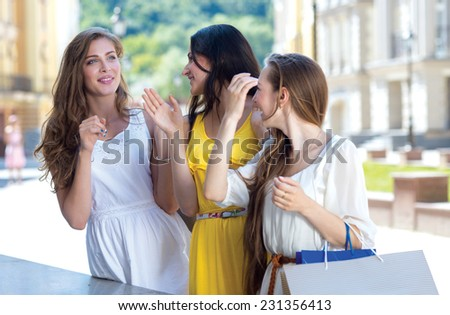 Talking with girlfriends about shopping trends. Three young and pretty girls are standing with shopping bags and talking to each other about best offers and sales prices in a shops - stock photo