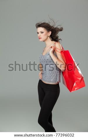tall brunette woman shopping bag wind hair - stock photo