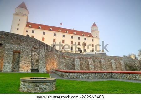 Tall building of Bratislava castle surrounded by green meadow, Slovakia - stock photo