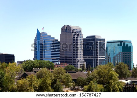 Tall buildings show above the tree in a skyline view of the city of Sacramento, California. - stock photo