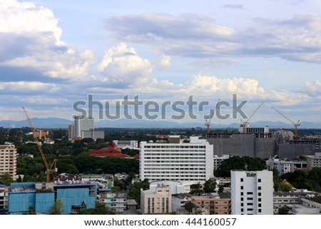 tall buildings under construction and cranes under a blue sky - stock photo