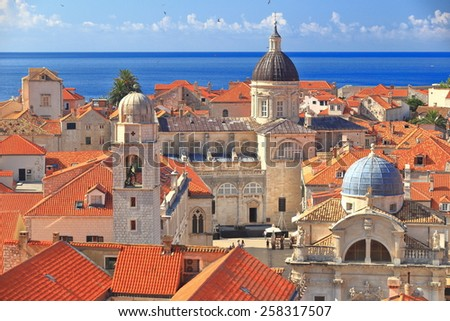 Tall church domes and the medieval clock tower above roof tops inside Dubrovnik old town, Croatia - stock photo