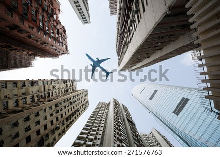 Tall city buildings and a plane flying overhead - stock photo