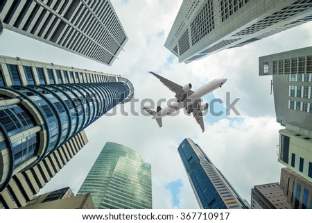 Tall city buildings and a plane flying overhead in morning - stock photo