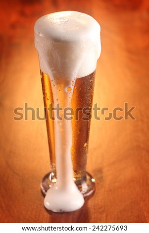 Tall elegant glass of beer with overflowing froth running down the side standing on a wooden bar counter, high angle view with highlight behind the glass - stock photo