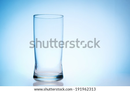 tall empty glass of water on blue background - stock photo