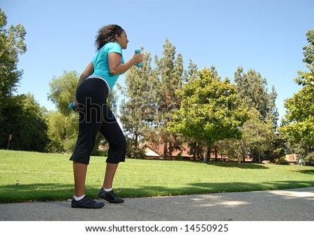 Tall fit young woman power walking in the park - stock photo