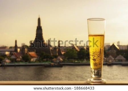 Tall glass of beer  with The background is a view of Wat Arun, Landmark in Bangkok. - stock photo