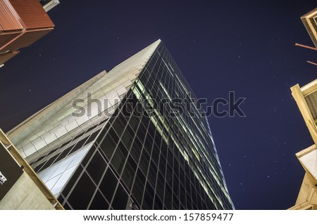 Tall glass office tower on a clear night - the BHP Billiton Centre in Melbourne, Australia. - stock photo