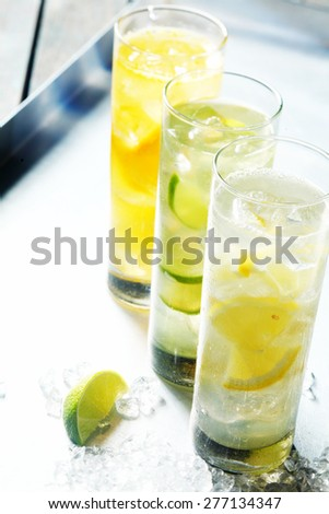 Tall glasses of iced citrus drinks for summer served on ice with fresh sliced fruit for a quenching beverage - stock photo