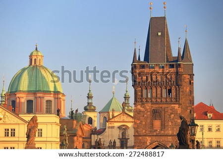 Tall Gothic tower and remote church rooftops under full moon, Prague, Czech Republic - stock photo