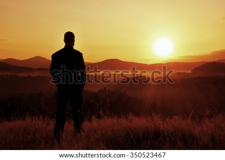 Tall hiker stand on meadow with golden stalks of grass and watch over misty and foggy morning valley to sunrise - stock photo
