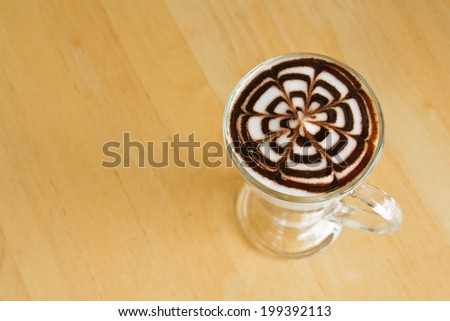 Tall latte glass on a wooden floor. - stock photo