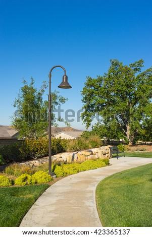Tall metal street light set above empty sidewalk in suburban park neighborhood. - stock photo