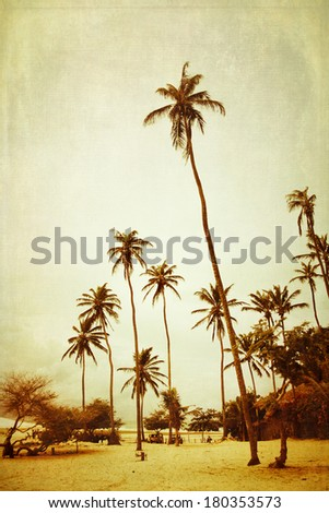 Tall palm trees on a beach, cross processed to look like an aged instant picture with texture - stock photo