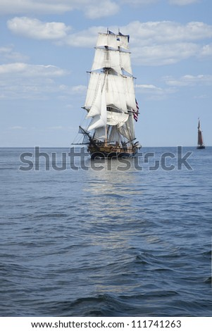 Tall ship sailing on blue waters - stock photo