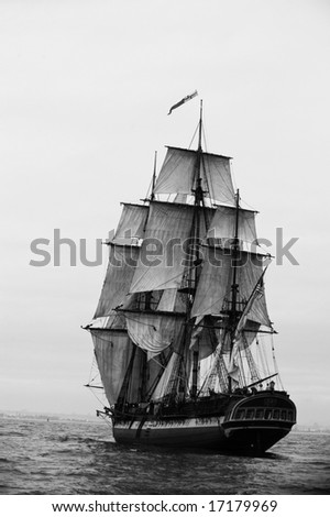 Tall Ship under sail moving into a fog bank - stock photo