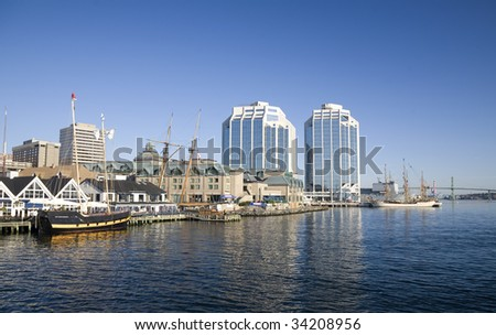 Tall ships docked in the early morning on Halifax's waterfront at Purdy's Wharf and farther down the waterfront during the Nova Scotia Tall Ship Festival 2009. - stock photo