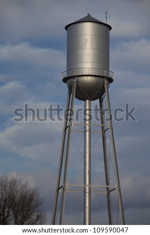 Tall silver water tower with cloudy blue sky background - stock photo