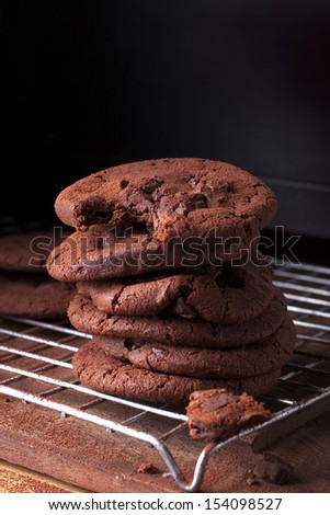 Tall stack of soft chocolate chip cookie with a bite mark. - stock photo