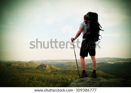 Tall tourist with poles in hand. Sunny evening in rocky mountains. Hiker with big backpack stand on rocky view point above misty valley.  Vignetting effect. - stock photo
