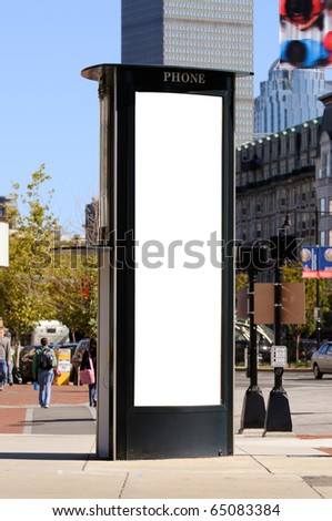 Tall, vertical billboard on phone booth, people walking by on the sidewalk and city street with traffic in the background. Clipping path included. - stock photo