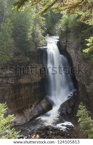 Tall waterfall in autumnal woods - stock photo