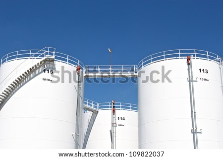 Tall white oil storage tanks - stock photo