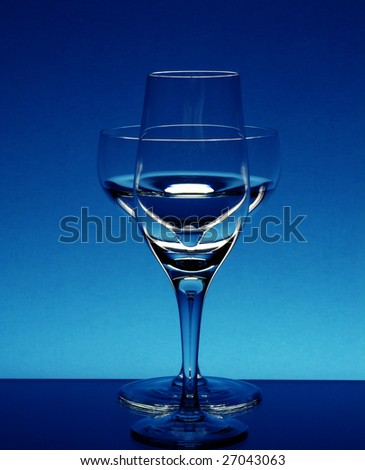 Tall wineglasses against a dark blue background - stock photo