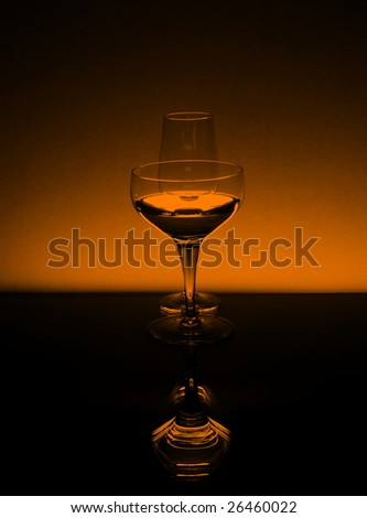 Tall wineglasses in black and orange against an orange background - stock photo