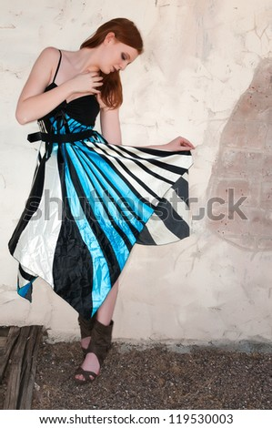 Tall young redhead in a blue, black and white dress - stock photo