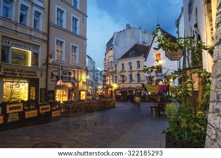 TALLINN, ESTONIA - AUGUST 29, 2015: Old buildings, restaurants and cafes in old historical area of the popular European city in Baltic region. Night view, cloudy sky. Lights and illumination - stock photo