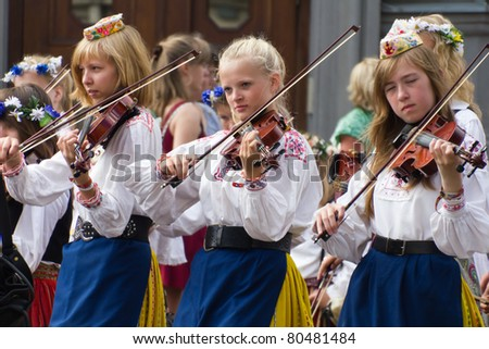 TALLINN, ESTONIA - JULY 3:Total unidentified of 22239 singers and 2111 orchestra players march on the parade of the 11th Youth Song and Dance Celebration in Tallinn, Estonia on July 3rd 2011. - stock photo