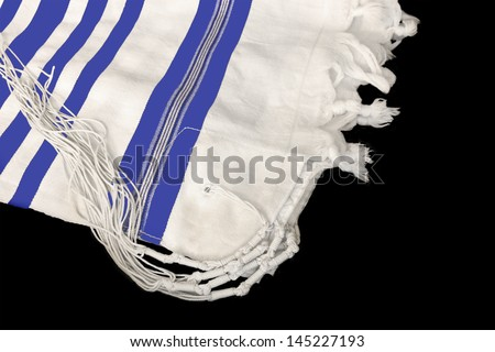 Tallit,Jewish prayer shawl for religious observance.White wool cloth garment,knots and fringes worn by Jewish men during prayer.Blue stripes indicate Sephardic style,custom. Isolated on black. - stock photo