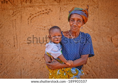 TAMALE, GHANA - MARCH 24: Unidentified old African woman holding baby on March 24, 2014 in Tamale, Ghana. African elders always take care for baby while young family's members go to work. - stock photo