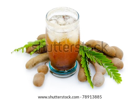 Tamarind juice in a glass surrounded by fresh ripe tamarinds and tamarinds leaves - stock photo